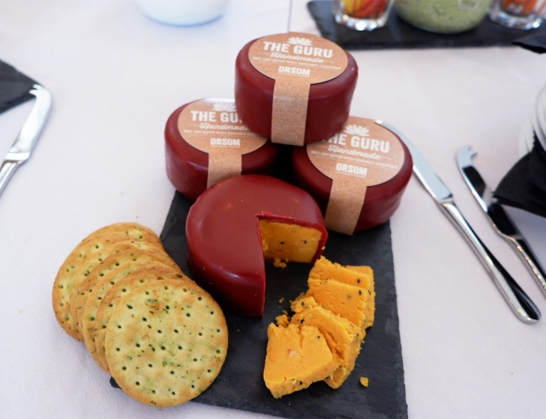 Three Guru cheeses stacked up as a tier the fourth cheese is cut displaying the red leicester cheese from inside, along the left crackers is on display