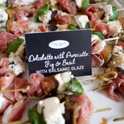 Dolcelatte with Prosciutto, Fig and Basil on skewers laid side by side each other with a label poking out of one of them