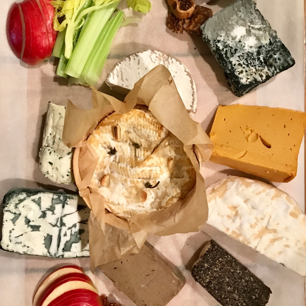 9 Vegan cheeses laid on a board with fruit and crackers surrounding them