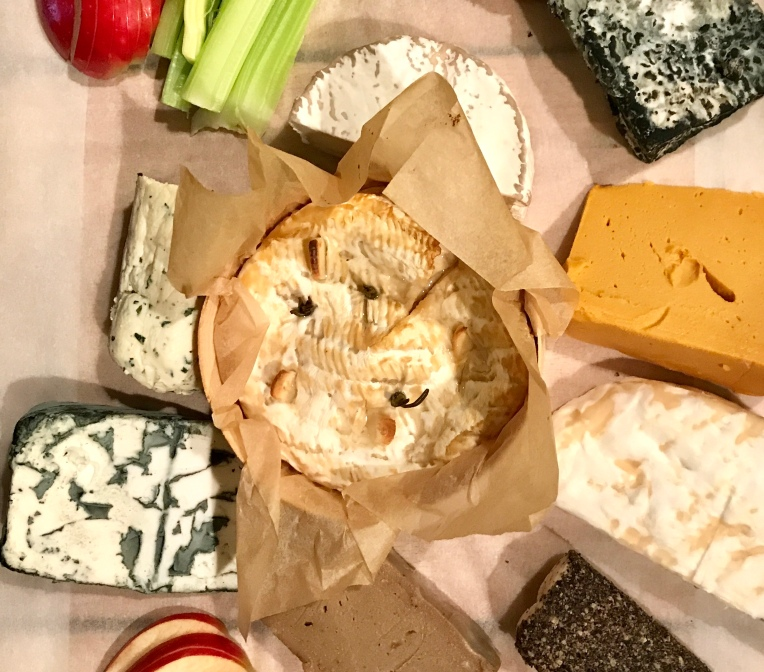 Baked vegan camembert, surrounded by other vegan cheeses