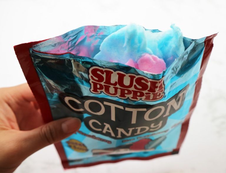 Candy floss packet is open with the pink and blue candy floss sticking out